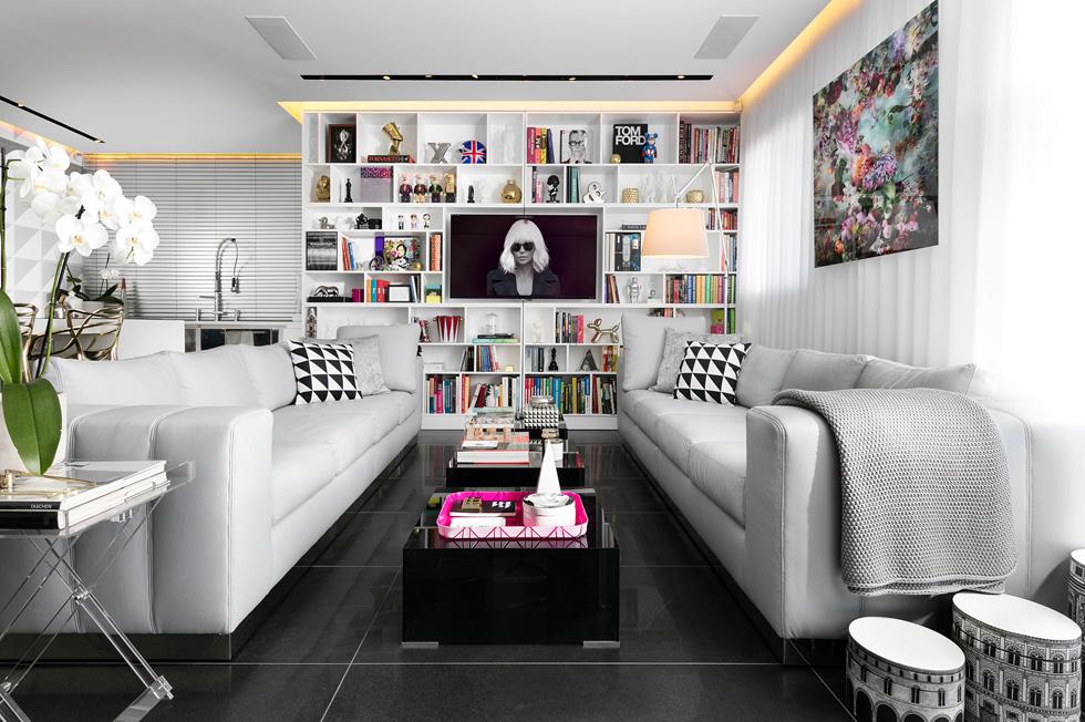 הרצפה כוסתה באריחים שחורים, ולסלון נבחרו ספות איטלקיות, שביניהן שולחנות קפה מזכוכית שחורה. ברקע ספרייה לבנה, שמציגה שלל חפצי חן (צילום: אלעד גונן)