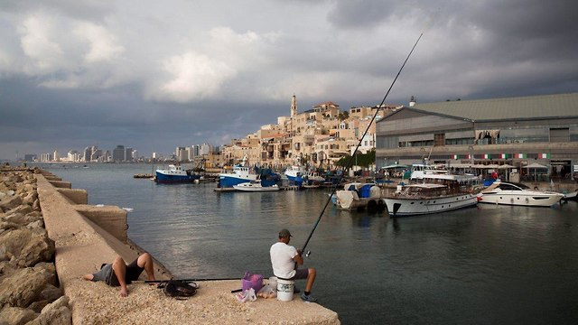A fisherman in Jaffa, Tel Aviv in the background