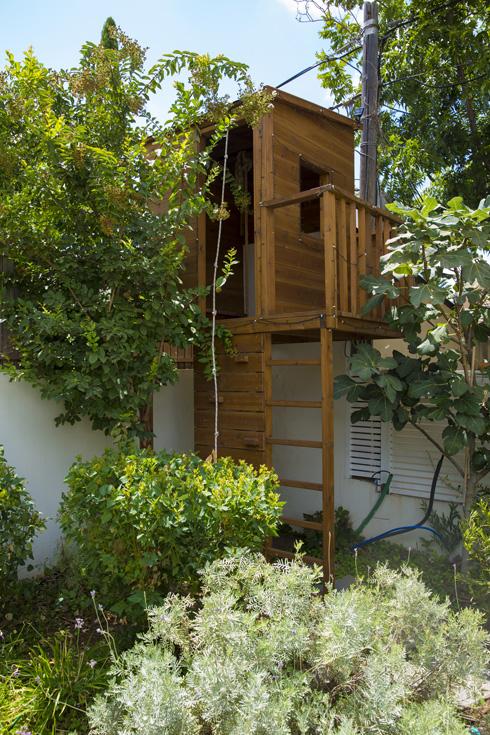 בחצר: בית עץ מדוגם לילדים עם חבל טיפוס ומדרגות חיצוניות (צילום: ענבל מרמרי)
