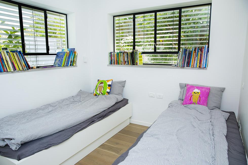 חדר השינה של התאומים גור ויאיר בני ה-9, עם כריות שעיצבו בעצמם בסדנה שערכה להם תושבת השכונה, האמנית דפנה אלון (צילום: ענבל מרמרי)