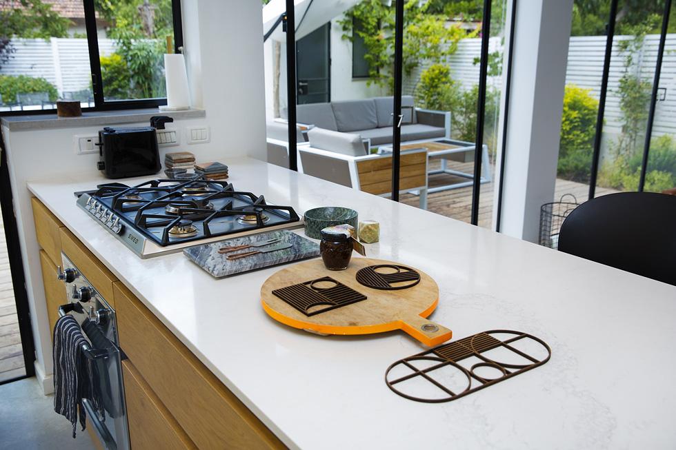 """""""הבר במטבח הוא גם המוקד שמארח חברים שמגיעים לבקר. הסלון מיועד יותר לצפייה בטלוויזיה"""" (צילום: ענבל מרמרי)"""
