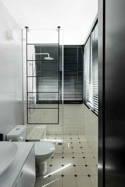 אותם חומרי גמר פשוטים חוזרים במקלחת ההורים. אריחי קיר לבנים, ריצוף מעוטר פסיפס שחור ומתלה מגבות מברזל, שיורד מהתקרה (צילום: גדעון לוין)