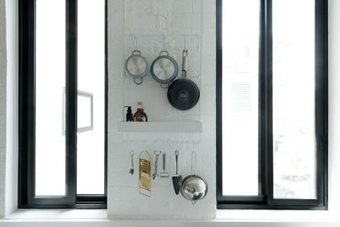 מוטות לתלייה של כלי בישול בין החלונות היחידים שפונים דרומה (צילום: גדעון לוין)