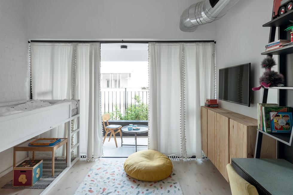 דלתות ויטרינה נפתחות למרפסת הפונה לגינה שבין הבניינים, וכך יש המשכיות בין הסלון לחדר ולמרפסת (צילום: גדעון לוין)