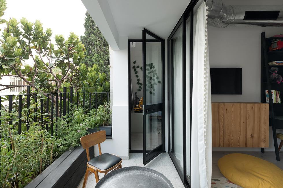 המרפסת רוצפה באריחי טראצו ונבנה בה ספסל עץ שחור עם אדנית שבה נשתלו צמחי תבלין וירקות (צילום: גדעון לוין)