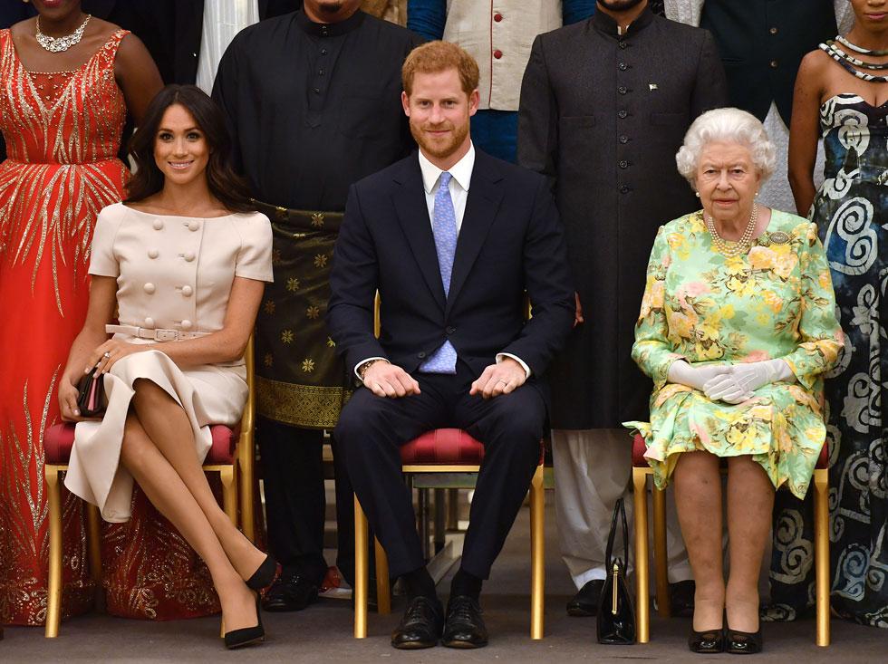 מייגן מרקל בחליפת חצאית של פראדה, שעוצבה עבורה במיוחד. לאחר שהסתבכה עם הרגליים בישיבה לצד המלכה, נותרת השאלה: האם צבעי פסטל מחמיאים לעור הפנים שלה?  (צילום: John Stillwell/GettyimagesIL)