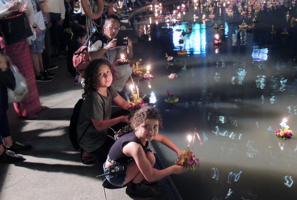 עמית ועומר משיטים סידור פרחים עם נר, כמנהג התאילנדי בחג לוי קרטונג בבנגקוק (צילום: שטרית בדרכים)