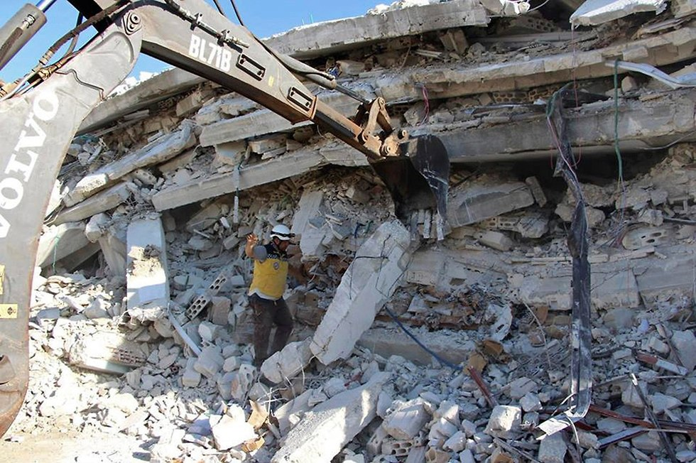 A member of the White Helmets searching for people in the ruins of a building (Photo: AP)