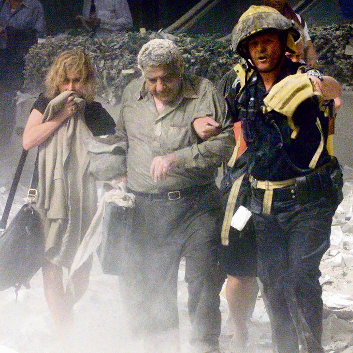 כבאי מסייע לניצולים להימלט מהזירה ומרסיסי ההרס