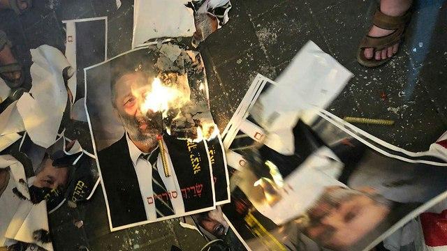 מפגינים שורפים תמונות של אריה דרעי (צילום: אור שרון,