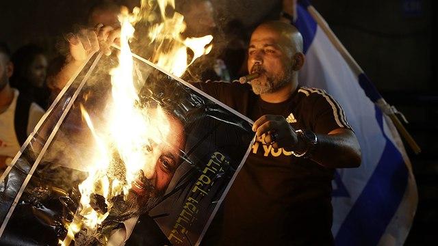 מפגינים שורפים תמונות של אריה דרעי (צילום: עמית שעל)