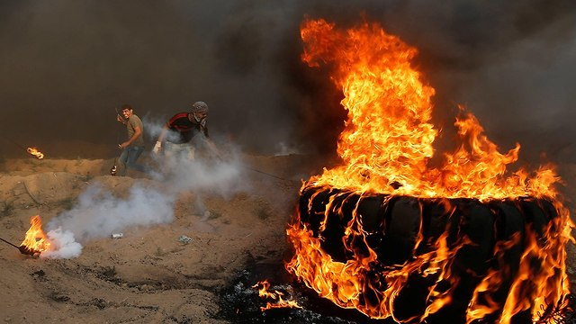 Palestinians burning tires during Gaza border protests (Photo: Reuters)