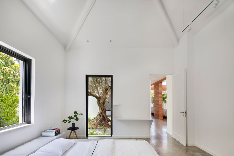 שני חדרים לבנות עוצבו בצורה זהה, מינימליסטית, עם חדר רחצה צמוד וחלונות שממסגרים את נוף החצר (צילום: אסף פינצ'וק)