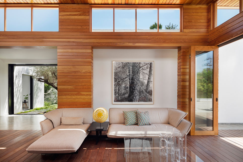 בסלון שתי פינות ישיבה ופינת אוכל. הוא פתוח משני צדיו בדלתות הרמוניקה מעץ, וחלונות סרט תוכננו במעלה הקירות (צילום: אסף פינצ'וק)
