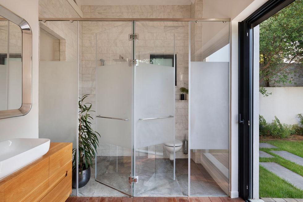 המקלחון ושירותי ההורים חופו שיש קררה והוסתרו מאחורי דלתות זכוכית שחלקן האמצעי אטום. מכאן יש יציאה ישירה לגינה (צילום: אסף פינצ'וק)