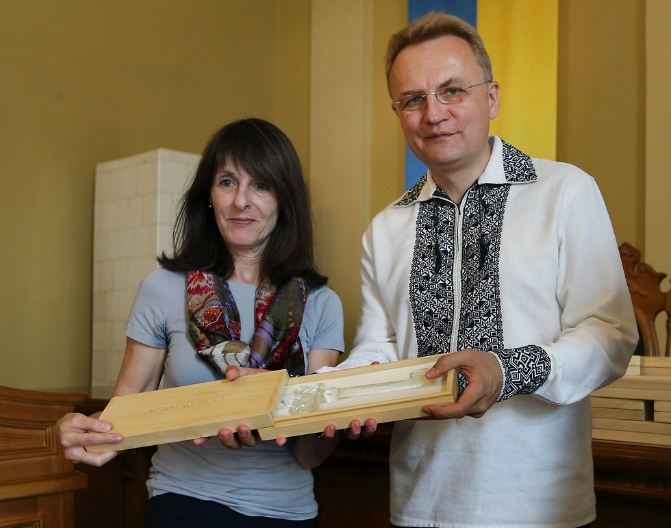 Marla Raucher Osborn, a Jewish heritage project leader, left, and Lviv Mayor Andriy Sadoviy, present a glass copy of an old metal synagogue key at a ceremony commemorating the 75th anniversary of the annihilation of the city's Jewish population by Nazi Germany in Lviv