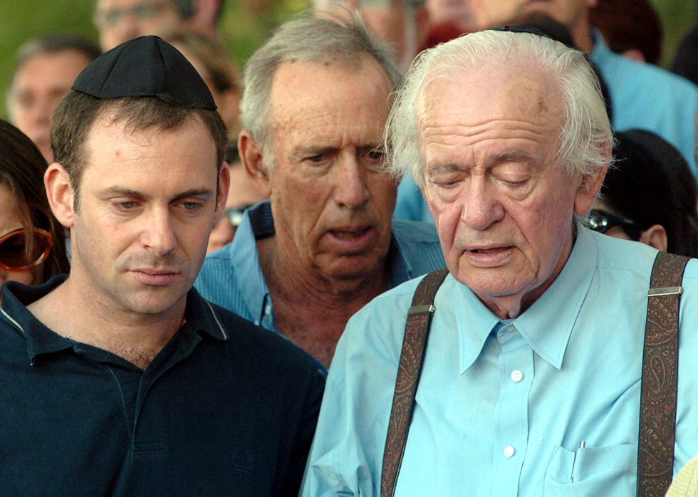 """ספיר בהלוויה של שמר, יוני 2004, בין בעלה, מרדכי הורוביץ, לבנה אריאל. למטה: שמר מבצעת את השיר """"אחינו הקטן"""" שכתבה עליו (צילום: אפי שריר)"""
