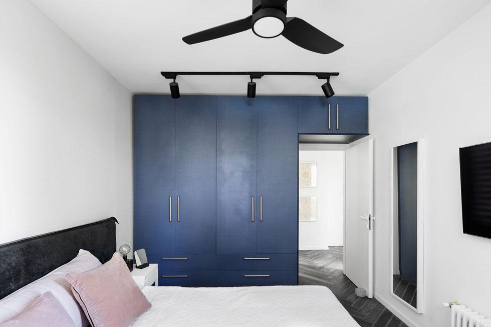 """חדר ההורים לא גדול. יש בו מיטה וארון קיר בצבע כחול כהה. על מקלחת פרטית ויתרו. """"היינו יכולים להכניס עוד חדר רחצה קטן, אבל לא ראינו בזה טעם בהתחשב בגודל הדירה ובמצבנו המשפחתי"""", אומרת האדריכלית אפרת וינרב, שהיא גם בעלת הדירה. בני הזוג מצפים כעת לילד ראשון  (צילום: איתי בנית)"""