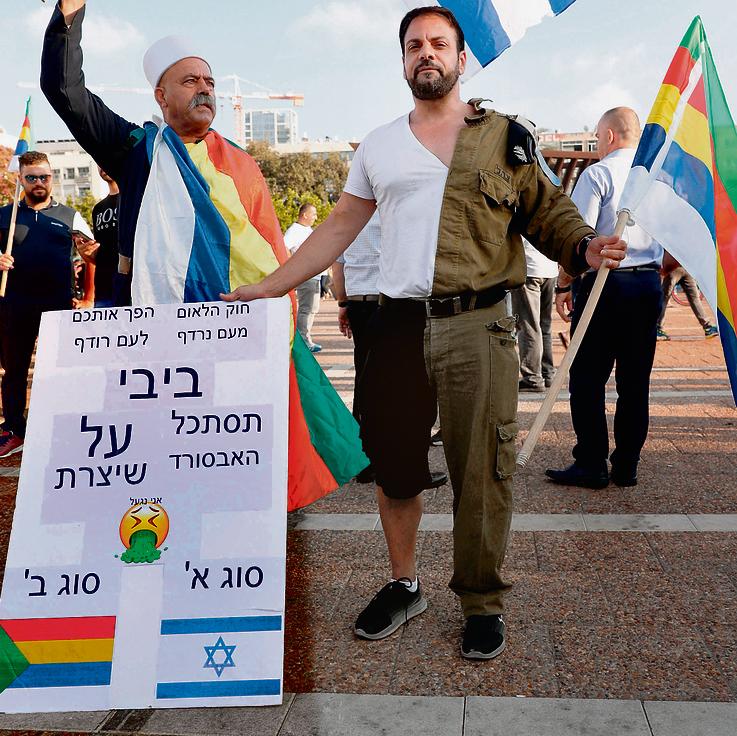 אחד ממשתתפי ההפגנה נגד חוק הלאום בכיכר רבין צילום: אי־אף־פי