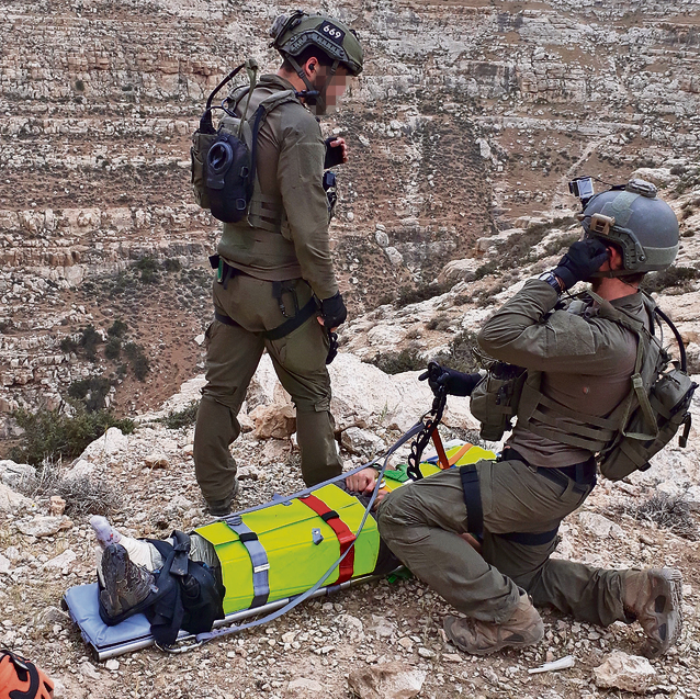 Guy and Yochai, treat an injured man in the Judean Desert shortly before they got the call to the Zafit Stream