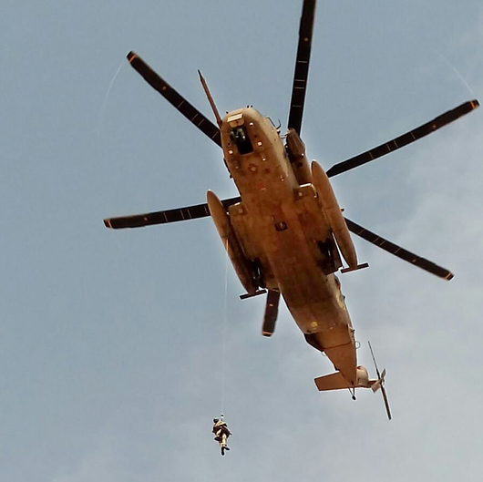 669 combat soldier lifts an injured man into a helicopter
