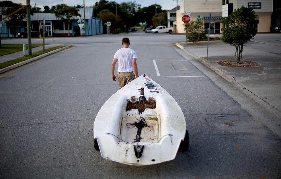 איש מזיז את הסירה שלו מהמרינה אל ביתו כדי שלא תנזק בהוריקן (צילום: AP)