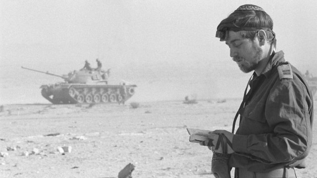 A religious officer praying during a lul in the battle (Photo: Defense Ministry Archives)