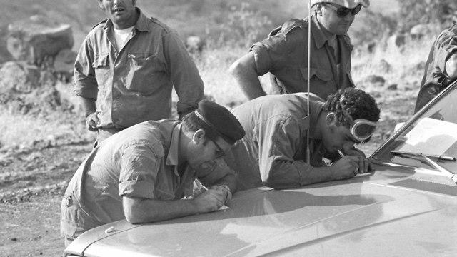 מלחמת יום הכיפורים חיילים רושמים מכתבים על קידמת רכב 6.10.1973 (צילום: במחנה  ,באדיבות ארכיון צה