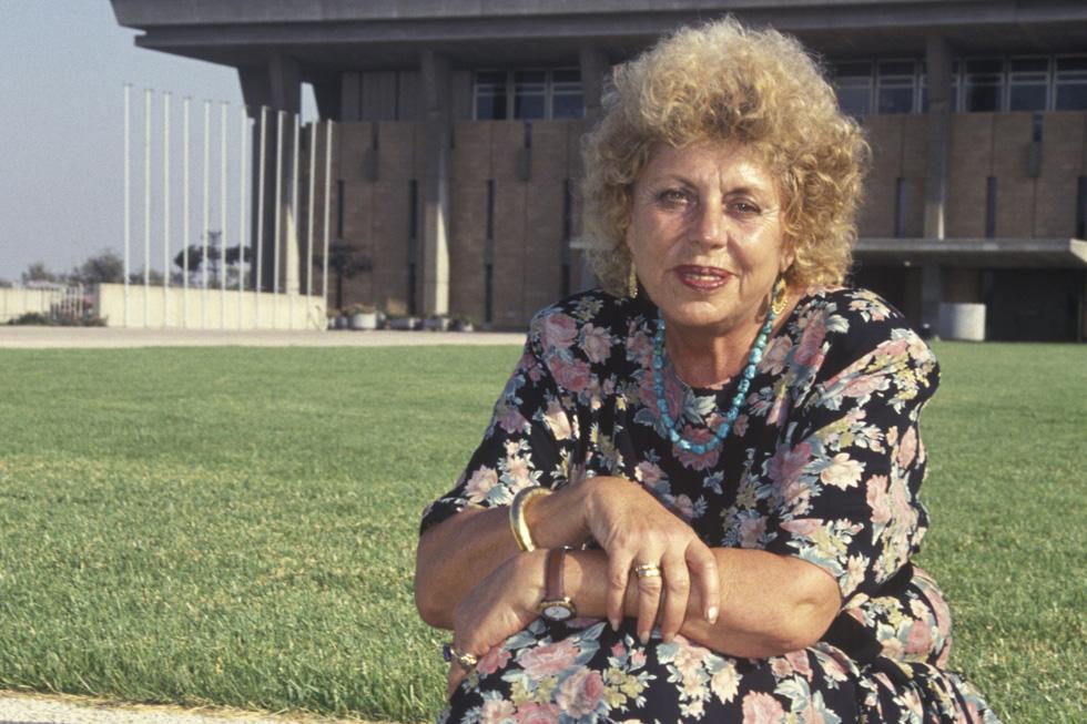 """שולמית אלוני על רקע משכן הכנסת, 1992. """"אמון העם לא אכפת לכם. העם לחוד והממשלה לחוד"""" (צילום: דוד רובינגר)"""
