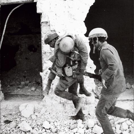 פנדריך (מימין) נושא את הרובה של חייל שנפצע באיסמאעיליה. בעוד שניות גם הוא עצמו ייפגע מרסיסים