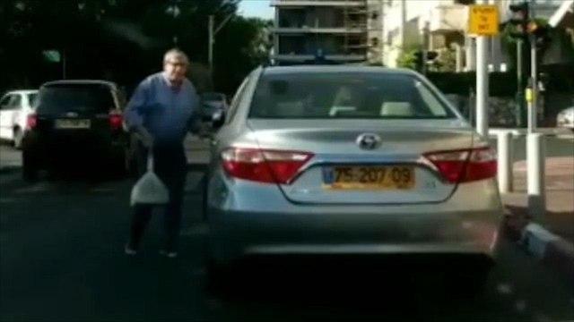 ראש עיריית רמת גן ישראל זינגר חונה באדום לבן ליד השלט