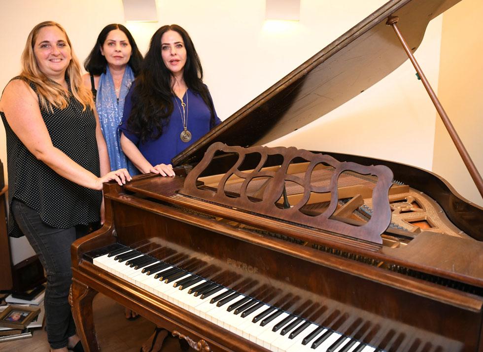 הבנות (מימין: טל, מיכל ושירה), בשבוע שעבר, ליד הפסנתר של אמן שעומד עכשיו בביתה של שירה. למטה: תוכנית טלוויזיה שהוקדשה לאילת (צילום: יאיר שגיא)