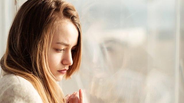 ילדה עצובה מביטה החוצה מהחלון (צילום: Shutterstock)