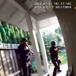 השוטרים דרוכים בחצר בזמן שטיילר האניקט מתבצר בבית