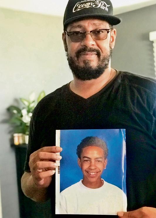 """האב, דארן האניקט, עם תמונה של בנו המנוח. """"טיילר תמיד רצה לעזור לי"""""""