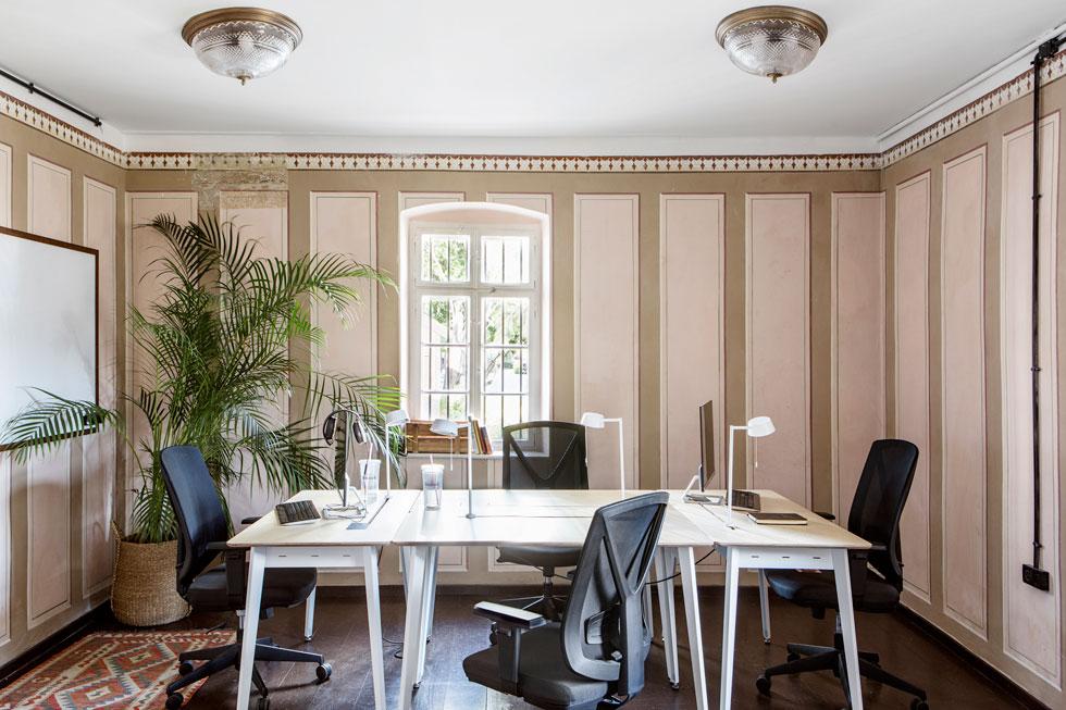 חדר העבודה המרכזי במשרדי ''למונייד'', בעיצוב פנינית שרת אזולאי. ציורי הקיר שוחזרו בשיפוץ הקודם, שולחנות העבודה הם של המותג הישראלי rack&tack (צילום: איתי בנית)