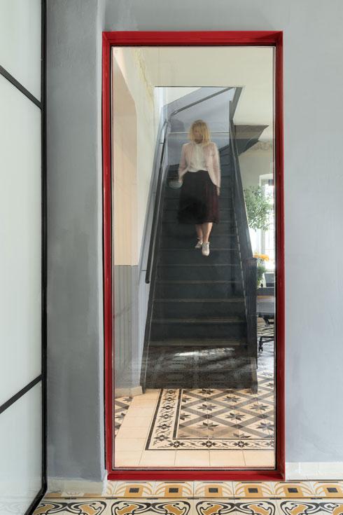 מבט מחדר הישיבות לעבר המדרגות לקומה השנייה, דרך חלון שנקבע בפתח קיים, בקיר שהוגדר לשימור (צילום: גדעון לוין)