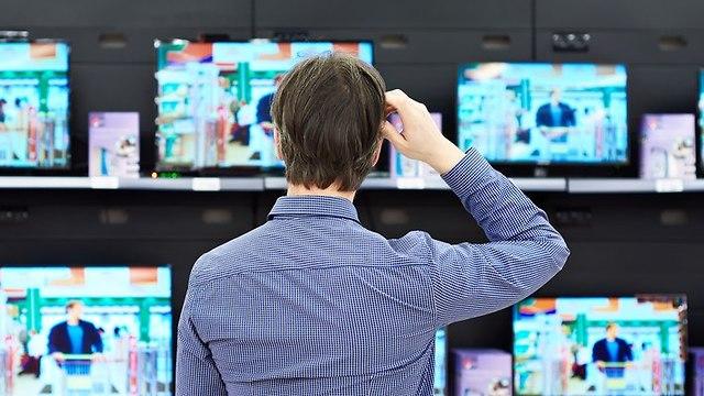 גבר מתלבט ברכישת טלוויזיה (צילום: shutterstock)