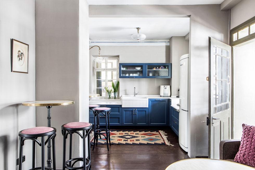 המטבח, עם משטחי עבודה בשני גבהים, הותאם לגובה החלונות. הכיור והארונות הכחולים, עם מסגרות מעוטרות, הולמים היטב מקרר בסגנון ישן (צילום: איתי בנית)