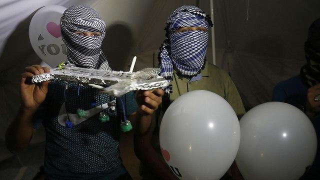 הכנה ושיגור של בלוני תבערה מעזה בלילה (צילום: AFP)