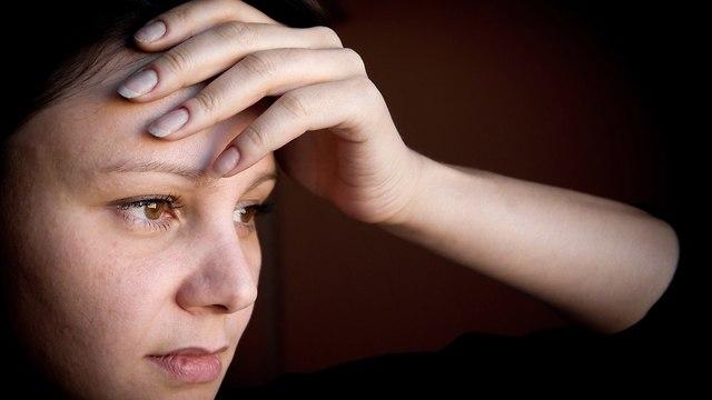 אשה עצובה עם יד על הראש (צילום: shutterstock)