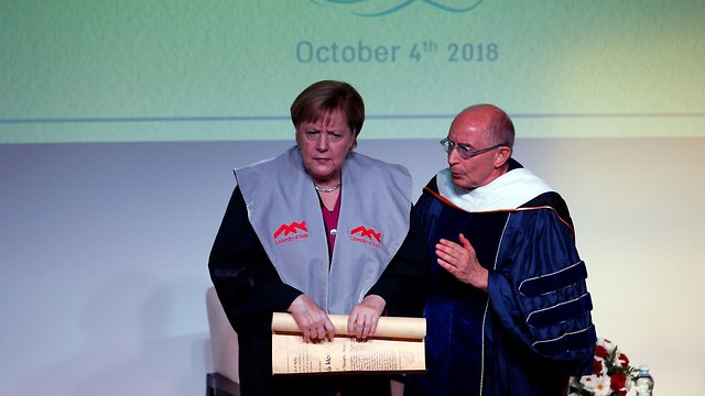Merkel receives honorary doctorate degree from Haifa University (Photo: Reuters)