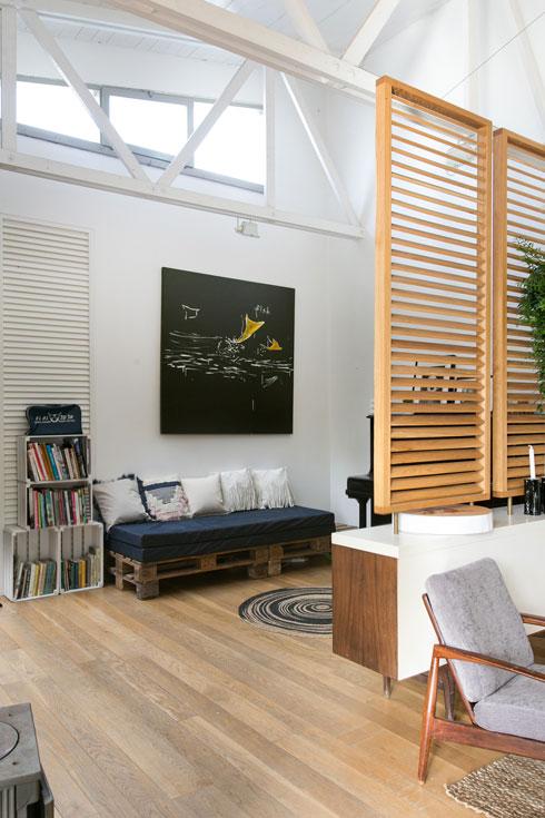 פרגוד קל מפריד פינת משפחה עם ספה ממשטחי עץ ישנים ומזרן (צילום: שירן כרמל)
