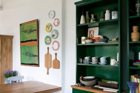על הקיר מקבץ צלחות קרמיקה מצוירות, קרשי חיתוך מגולפים ושתי עבודות אמנות גדולות של זהר בר אור, אחיה של בעלת הבית (צילום: שירן כרמל)