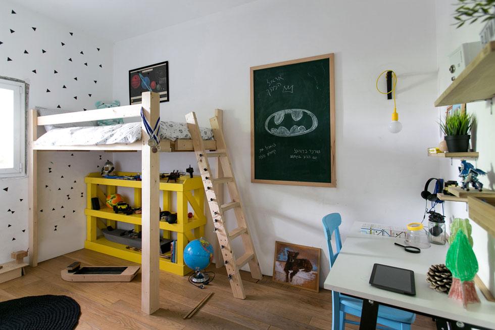 לכל ילד יש מרחב פרטי עם פינת לימוד קטנה ואפיונים אישיים.  לשני הבנים בנה האב מיטות מוגבהות עם סולם מעץ אורן פשוט ולא צבוע. החלל מתחת למיטות משמש כאזור משחק נוסף (צילום: שירן כרמל)