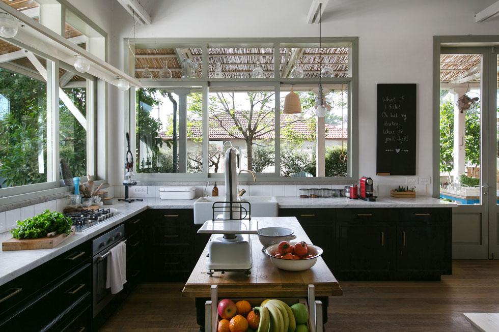 """המטבח """"בסגנון בראסרי"""", כפי שמגדירה הילה בלומנפלד, בעלת הבית, שגם עיצבה את הפנים. שתי צלעותיו פונות עם חלונות גדולים לגינה, שבה ניטעו עצים בוגרים לפני שהבנייה החלה. במטבח ארונות שחורים עם מסגרות בסגנון צרפתי. הכיור הוא אמבט חרסינה, שבן זוגה, הנגר אסף בלומנפלד, מצא (צילום: שירן כרמל)"""