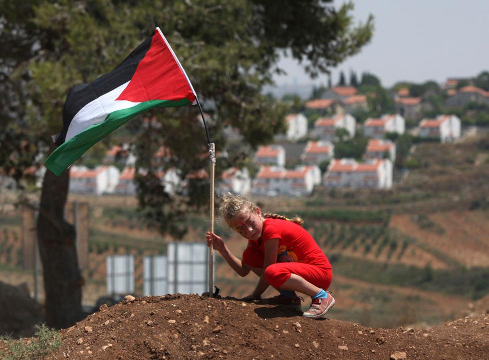"""""""אילו הותר לי להיות נערה רגילה שחיה בארץ רגילה, הייתי משחקת ספורט"""". תמימי עם דגל פלסטין בשנת 2011 (צילום: AP)"""