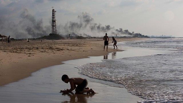 ישראלים בחוף זיקים ברקע עשן שריפת צמיגים ברצועת עזה (צילום: AP)