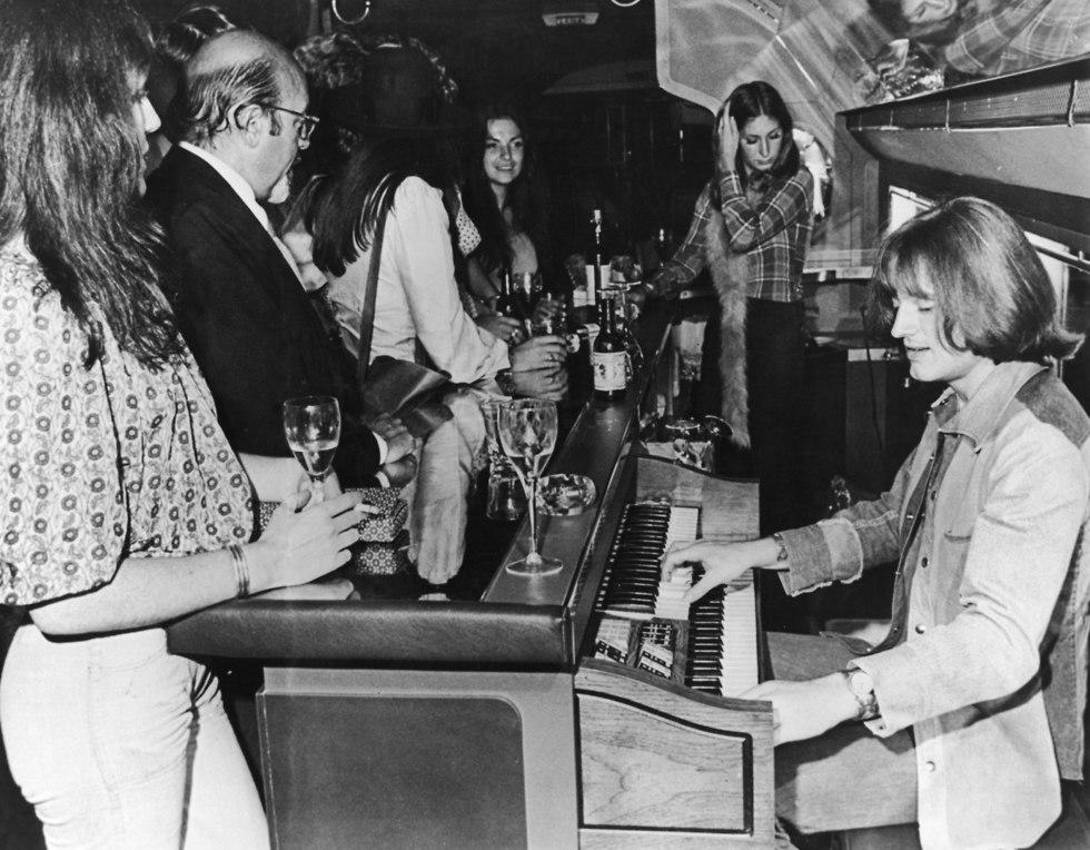 ג'ון פול ג'ונס מנגן בבר במטוס הפרטי של הלהקה (צילום:  Daily Express/Hulton Archive/GettyImagesIL)