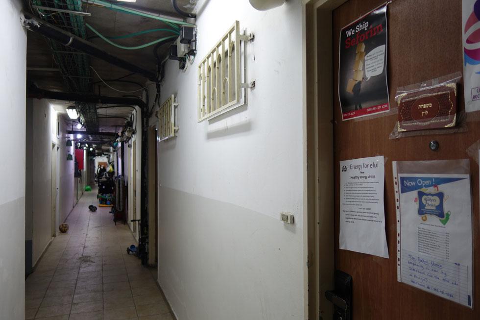 חלונות קטנים ומסורגים פונים למסדרון המחסנים בקומת החניון באחד מבנייני המגורים בירושלים. על הדלתות לוחות עם שמות המשפחה (צילום: מיכאל יעקובסון)